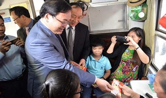 Bí thư Thành ủy Hà Nội Hoàng Trung Hải mừng tuổi và chúc năm mới khách đi tàu. Ảnh: An ninh Thủ đô.