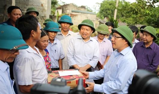 Phó Thủ tướng Phạm Bình Minh động viên, tặng quà các gia đình có hoàn cảnh khó khăn bị thiệt hại do mưa lũ. Ảnh: VGP