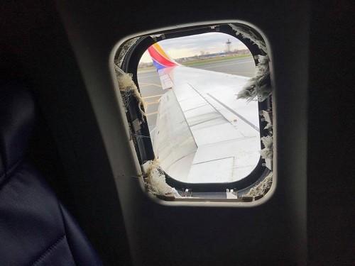 Cửa kính bị vỡ, hút một phụ nữ ra ngoài nhưng các hành khách đã kéo bà này lại. Ảnh: Facebook.