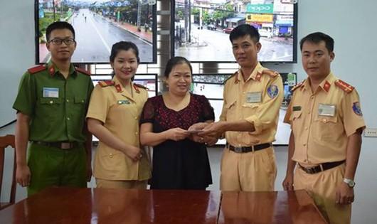 Các chiến sĩ Cảnh sát giao thông giao trả tiền cho bà Hoàng Thị Bích Thủy. Ảnh: Cổng thông tin Bộ Công an