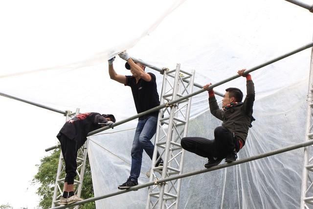 Mặc dù trời mưa và thời tiết lạnh nhưng công việc lắp đặt chiếc màn hình LED rộng 40m2 vẫn được tiến hành.