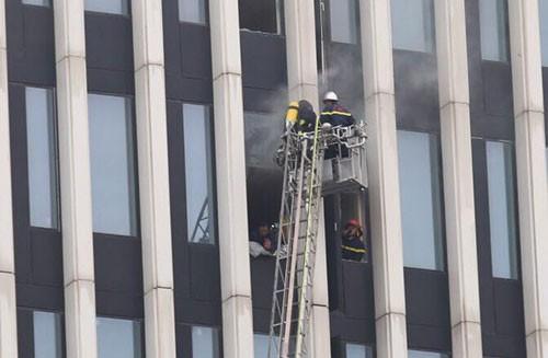 Cảnh sát cứu hỏa đập kính để tiếp cạn đám cháy. Ảnh: Gia Chính