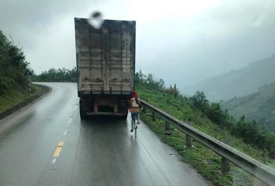 Kinh hãi nữ sinh đi xe đạp liều mạng bám tay vào đuôi Container khi vượt đèo - Ảnh 1.