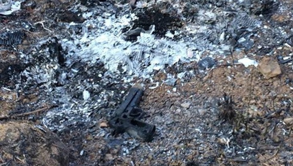 Khẩu súng bị đốt cháy tại khu vực hoang vắng. Ảnh: Công an tỉnh Đồng Nai.