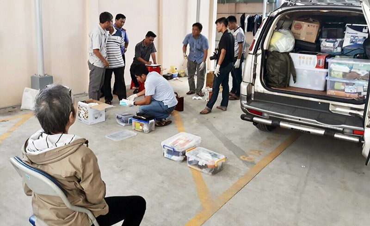 Trịnh Thị Hồng Hoa (66 tuổi) - người lớn tuổi nhất trong nhóm nghi can ngồi chứng kiến cảnh sátkhám xét ôtô 7 chỗ. Ảnh: Nguyệt Triều.