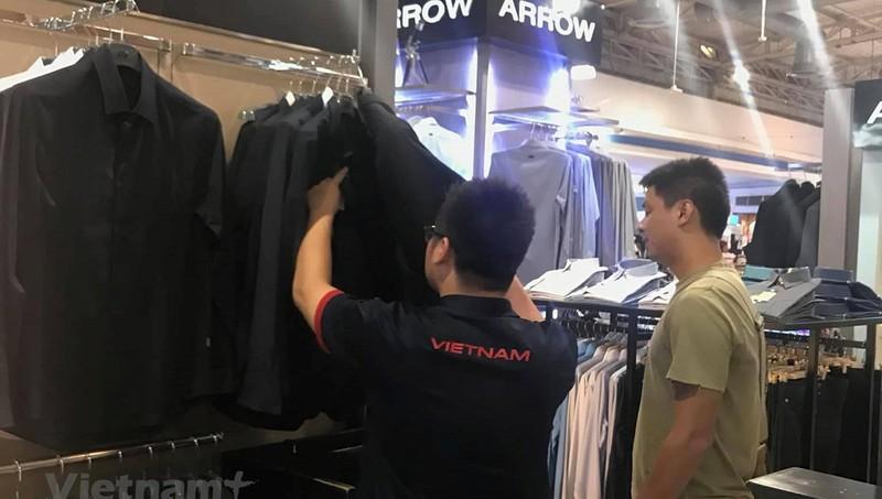 Phóng viên Việt Nam đi mua vest để tác nghiệp ở trận chung kết King's Cup 2019. (Ảnh: H.H.H/Vietnam+)