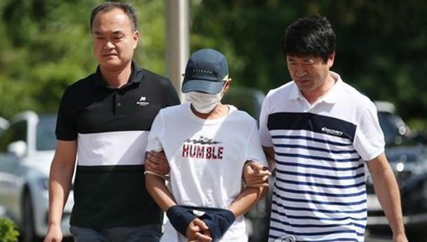 Nghi phạm bạo hành vợ người Việt là chị L.N.T.G bị áp giải ra tòa án thành phố Gwangju, tỉnh Nam Jeollan hôm 8/7. (Ảnh: Yonhap)