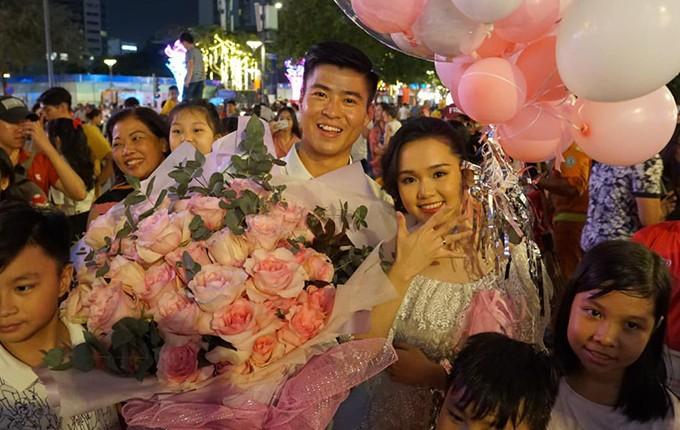 Duy Mạnh và bạn gái Quỳnh Anh chụp ảnh cùng người hâm mộ sau màn cầu hôn tại phố đi bộ Nguyễn Huệ, TP HCM.