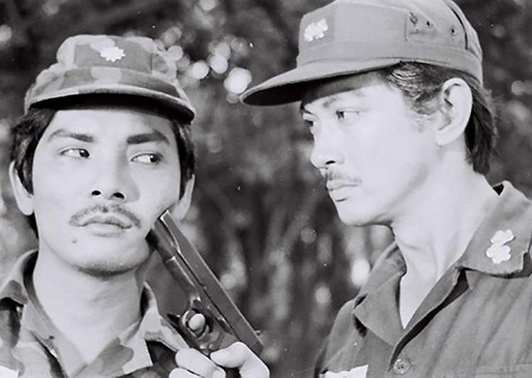 Thương Tín (trái) bên Chánh Tín trong một cảnh quay của Ván bài lật ngửa. Ảnh: Hãng phim Giải Phóng./