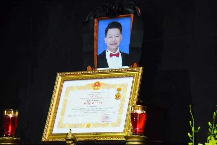 Ca sĩ Vũ Mạnh Dũng nhận danh hiệu Nghệ sĩ Ưu tú tháng 9 năm ngoái. Tấm bằng được người thân đặt trước di ảnh anh trong lễ tang. Ảnh: Giang Huy.