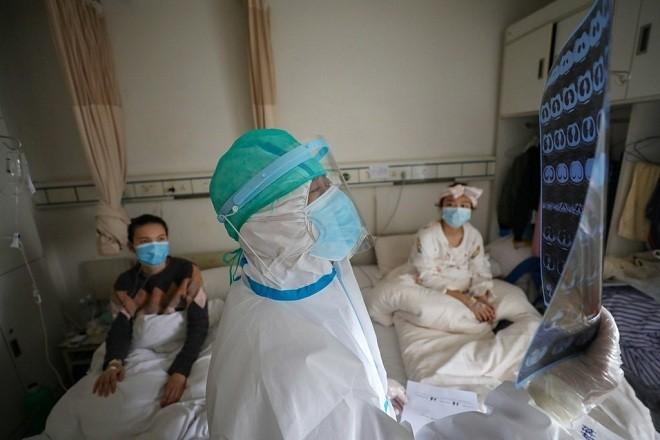 Nhân viên y tế Bệnh viện Chữ thập đỏ tỉnh Hồ Bắcđọc kết quả chụp CT phổi của các bệnh nhân tại khu cách ly. Ảnh: Reuters