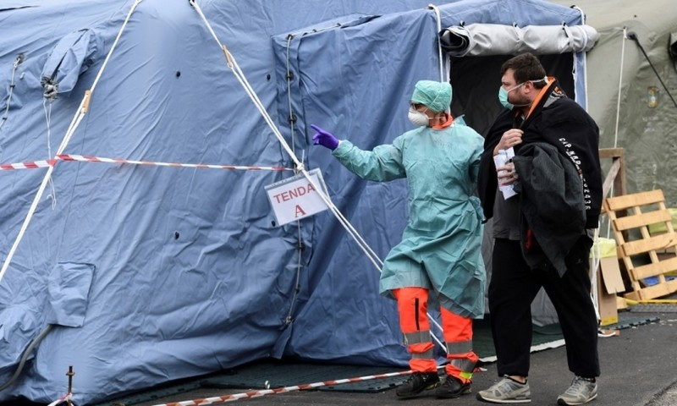 Nhân viên y tế Italy chỉ dẫn bệnh nhân tới khu xét nghiệmtại bệnh viện Brescia, vùng Lombardy, hôm 13/3. Ảnh: AFP.