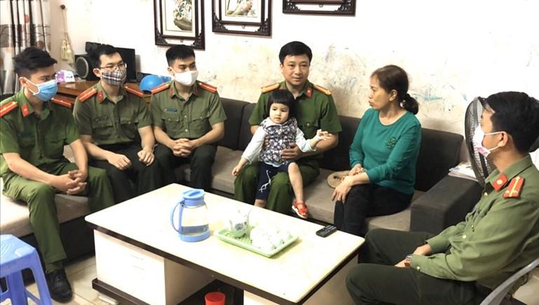 Trung tá Trương Thụy Hải (bế cháu bé) cùng cán bộ chiến sỹ Công an huyện Văn Bàn đến thăm cháu bé sau 2 ngày ra viện. Ảnh: Công an tỉnh Lào Cai.