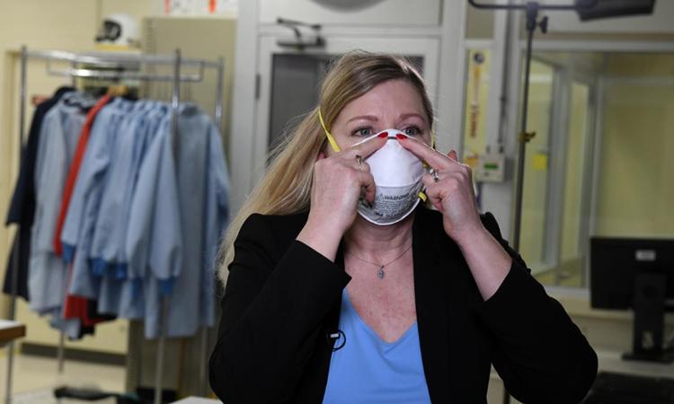 Tiến sĩ Nicole McCullough, chuyên gia y tế và sức khỏe toàn cầu của công ty 3M, hướng dẫn cách đeo khẩu trang N95 đúng cách trong phòng thí nghiệm công ty hôm 4/3. Ảnh: Reuters.