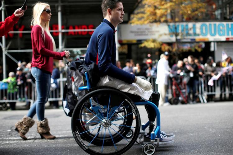Kolfage mất hai chân và tay phải trong cuộc chiến ở Iraq, đi diễu hành cùng vợ trong ngày kỷ niệm Cựu Chiến binh tại quảng trường số 5 ở New York tháng 11/2014. Ảnh: Mike Segar.