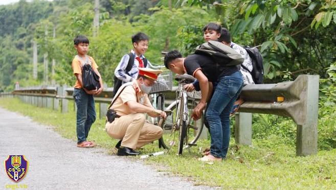 'Đốn tim' hình ảnh chú cảnh sát ngồi bên đường sửa xe cho học sinh