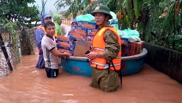 Ông Phan Thanh Miên (phải) dầm mưa, lội nước lũ cùng các đoàn cứu trợ đi cấp phát nhu yếu phẩm tiếp tế cho bà con trong đợt mưa lũ lịch sử vừa qua.