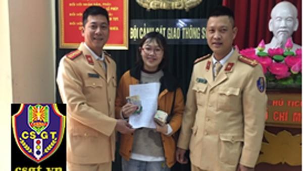 Nữ sinh viên vui mừng khi nhận được tài sản bị mất. Ảnh: Cục CSGT.