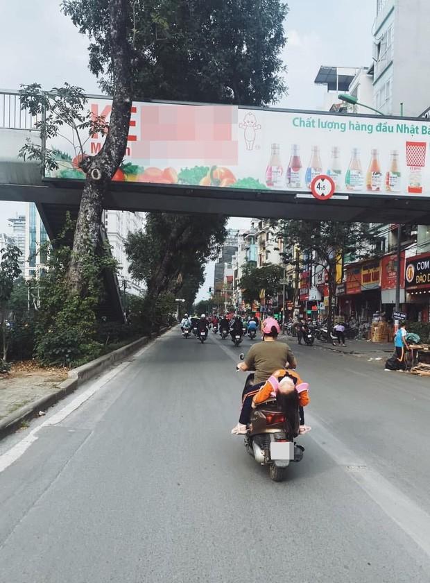 Hình ảnh bé gái ngủ gục, nằm hẳn ra yên xe máy trên phố Hà Nội khiến ai cũng phải thót tim - Ảnh 1.