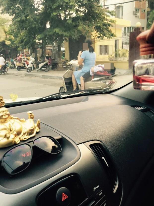 Hình ảnh bé gái ngủ gục, nằm hẳn ra yên xe máy trên phố Hà Nội khiến ai cũng phải thót tim - Ảnh 2.
