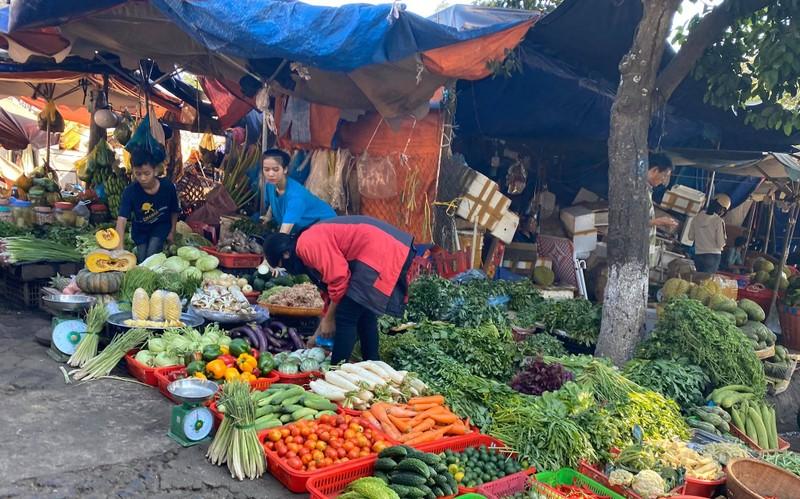 Tiểu thương ở một sạp rau chợ Tân An không đeo khẩu trang khi bán hàng