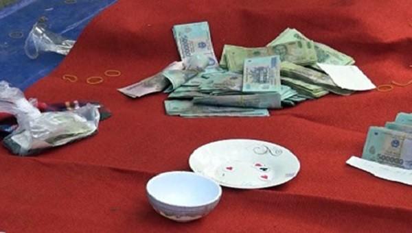 Dụng cụ đánh bạc và số tiền cơ quan công an thu được tại chiếu bạc.