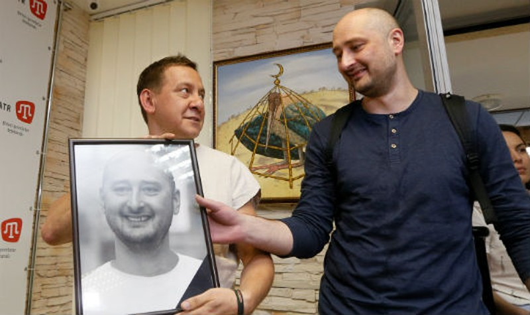 Babchenko cầm bức ảnh chân dung của mình mà các đồng nghiệp đặt tại góc tưởng niệm ôngở văn phòng kênhATR TV, Kiev hôm 31/5