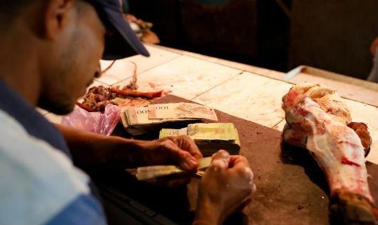 Cả xấp tiền bolivar chỉ mua được một khúc xương. Ảnh chụp tại một hàng thịt ở Maracaibo, Venezuela ngày 26/07/2018