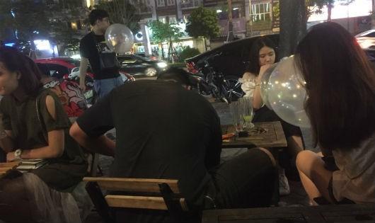 Các bạn trẻ hút bóng cười ở quán cafe trên phố Xã Đàn (quận Đống Đa, Hà Nội).