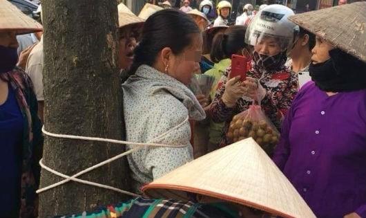 Hình ảnh người phụ nữ bị trói vào gốc cây