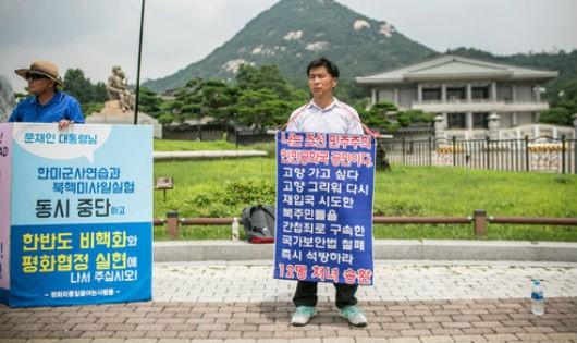"""Ông Kwon Chol-nam, người Triều Tiên đào tẩu sang Hàn Quốc năm 2014, giương tấm biển với hàng chữ """"Tôi là công dân của Cộng hòa Dân chủ Nhân dân Triều Tiên. Tôi muốn trở về nhà"""""""