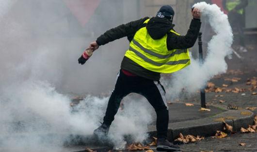 Một người biểu tình ném trả lựu đạn hơi cay về phía cảnh sát ở Paris hôm 1/12