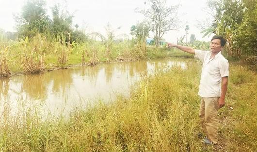 Ông Huỳnh Văn Thành bên khu vườn cây cối đang chết dần.