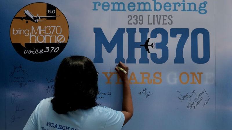 Một thân nhân của hành khách trên chuyến bay MH370 viết lên tấm bảng trong sự kiện tưởng niệm 5 năm máy bay mất tích.