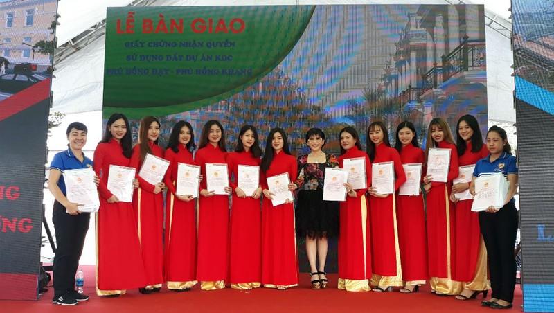 Bà Phạm Thị Hường (đứng giữa) – Chủ tịch Công ty BĐS Phú Hồng Thịnh trao sổ đỏ cho khách hàng.