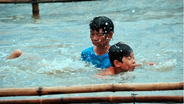 Bà Thia quên đau nhức xương khớp để dạy bơi cho lũ trẻ trong vùng