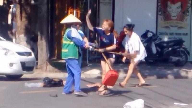 Nữ lao công bị đánh sau khi nhắc nhở chủ shop bỏ rác đúng nơi quy định. Ảnh cắt từ clip.