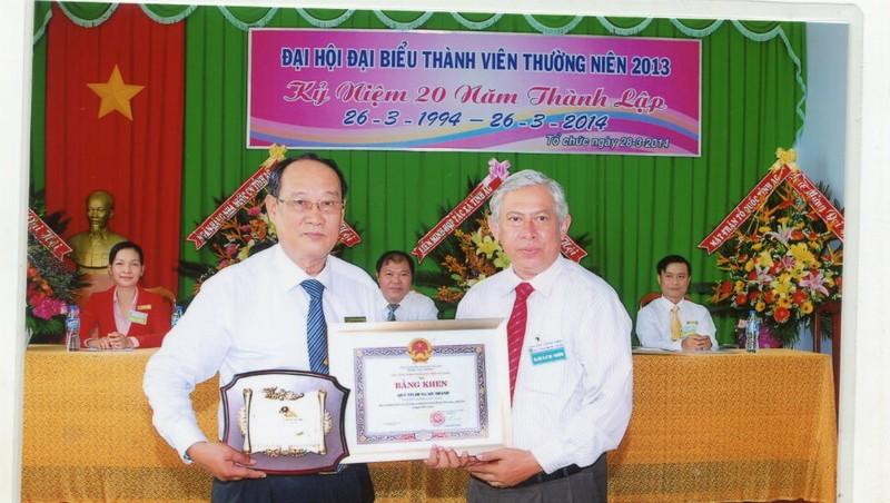 Ông Đỗ Vi Tân - Chủ tịch Hội đồng quản trị Quỹ tín dụng nhân dân Mỹ Thạnh (trái) nhận Bằng khen của UBND tỉnh An Giang