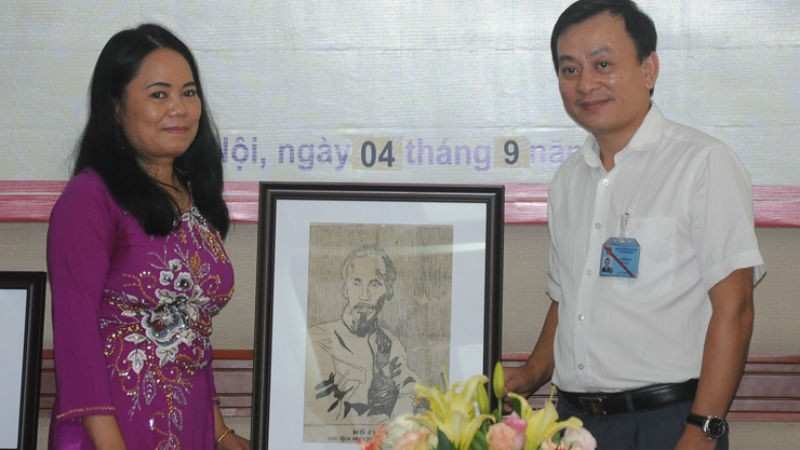 Ông Vũ Mạnh Hà (phải) Giám đốc Bảo tàng Hồ Chí Minh tiếp nhận bức tranh chân dung Bác Hồ từ dịch giả Hiệu Constant.