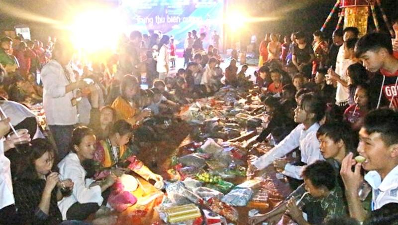 Trẻ em ở Phố Bảng, Hà Giang phá cỗ trông trăng cùng với các cô giáo và cán bộ, chiến sĩ Báo Biên phòng và BĐBP. Ảnh Kim Nhượng