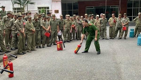 Cảnh sát PCCC CAQ Đống Đa (Hà Nội) hướng dẫn lực lượng bảo vệ dân phố, dân phòng sử dụng bình chữa cháy.