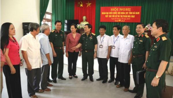 Đại tướng Ngô Xuân Lịch và các đại biểu, cử tri trao đổi bên lề hội nghị. Ảnh: BQP.