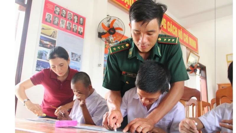Thầy giáo Chính và cô giáo Ly cầm tay dạy các em từng chữ một. Ảnh: Hồng Anh