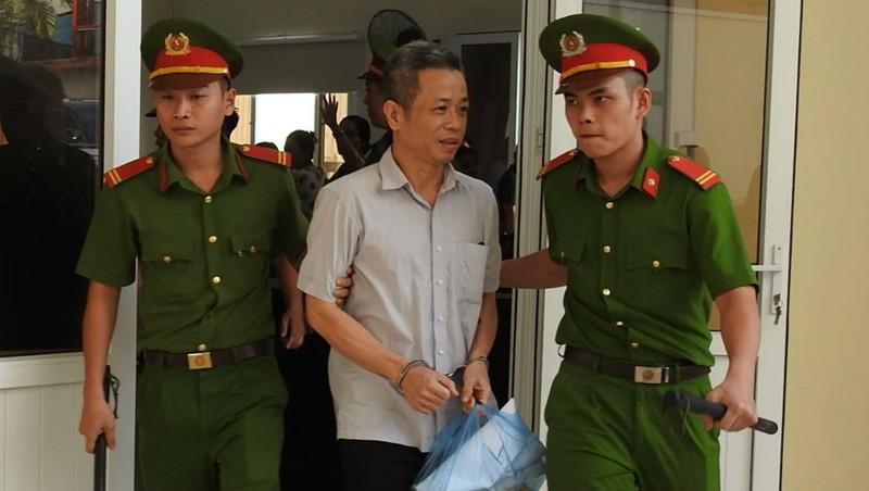 """Sau khi tòa tuyên """"nghị án kéo dài"""", ông Khanh bị dẫn giải về trại giam."""