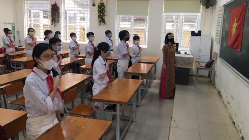 Học sinh chào cờ trong lớp ngày đầu đến trường.