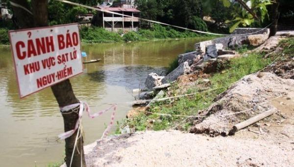 Biển cảnh báo tại khu vực sạt lở bờ tả sông Bùi, đoạn qua xã Hòa Chính, huyện Chương Mỹ.  Ảnh: T.Tùng