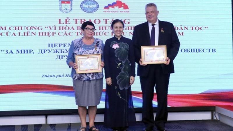 Bà Nguyễn Phương Nga trao tặng Kỷ niệm chương cho ông Aleksei Vladimirovich Popov và bà Natalia Borisovna Zolkina. (Ảnh: Xuân Khu/TTXVN).