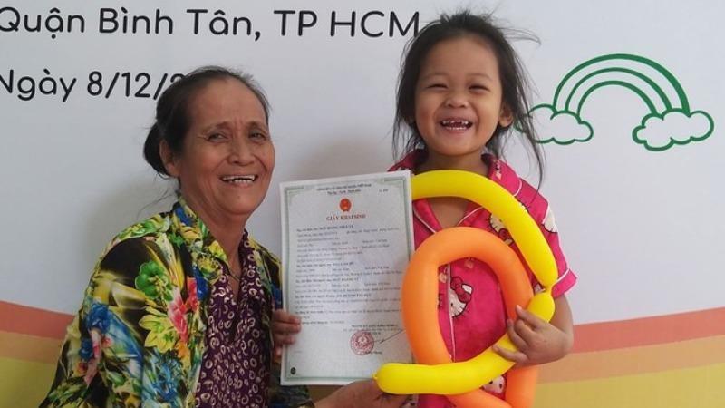 Bà cháu bé Thúy Vy vui mừng với giấy khai sinh của bé.