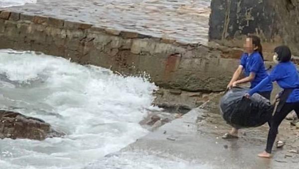 Nhân viên quán cà phê ném rác xuống biển.