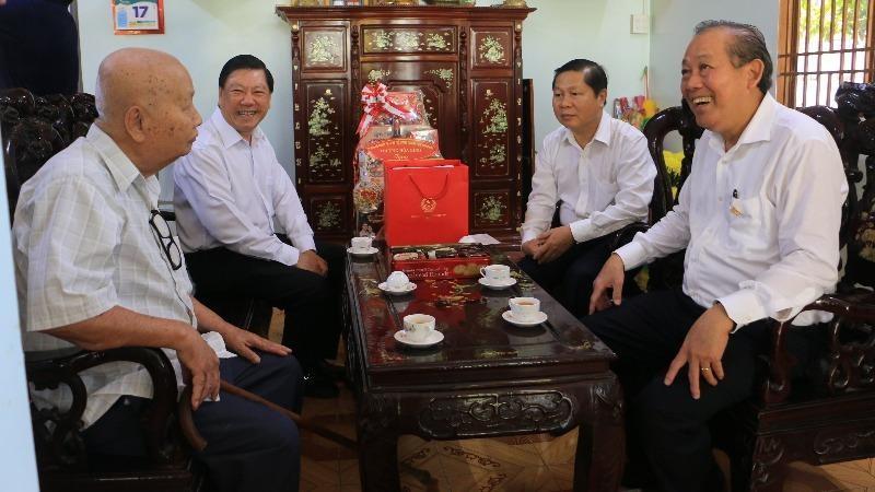 Phó Thủ tướng Thường trực Chính phủ Trương Hòa Bình (bìa phải) và ông Trần Văn Rón, Bí thư Tỉnh ủy Vĩnh Long (thứ 2 từ trái sang) thăm và tặng quà cho gia đình chính sách.